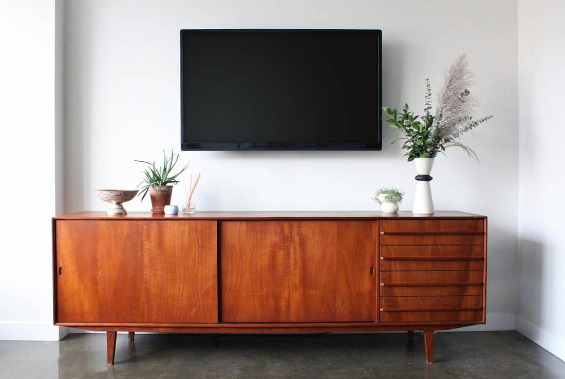 A 50 inch flat screen TV wall is mounted above a mid century modern teak credenza