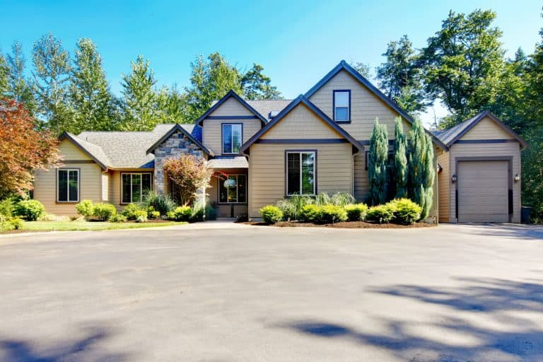 A huge two storey house with brown sidings and black windows with a huge driveway, What Color Siding Goes With Black Windows?