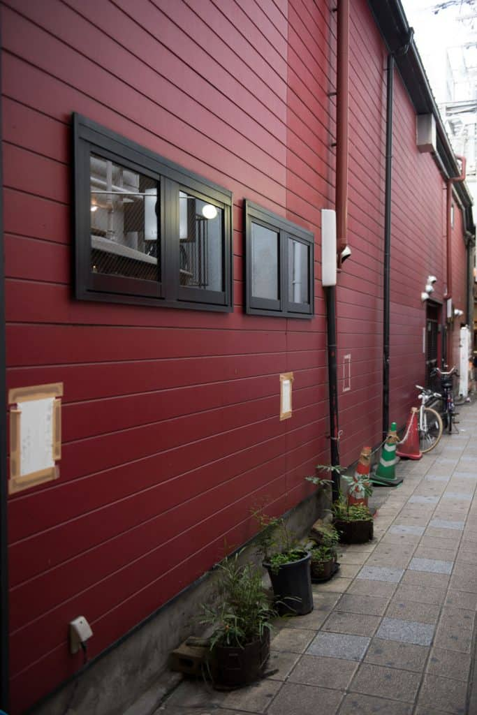 A long span barnhouse with red wooden sidings, black window awnings and small plants on the side