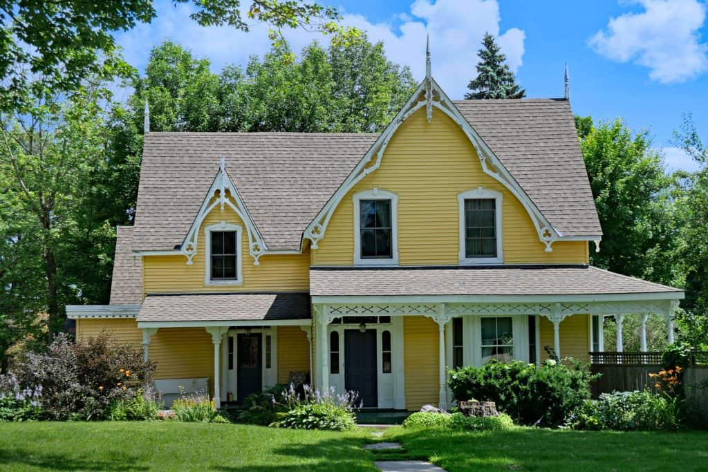 A two storey country home with black windows, yellow sidings and gorgeous landscaping