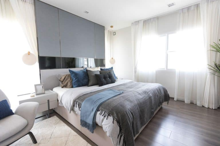 An elegant interior of a modern bedroom with hardwood flooring and white curtains, Which Way Does A Flat Sheet Go?