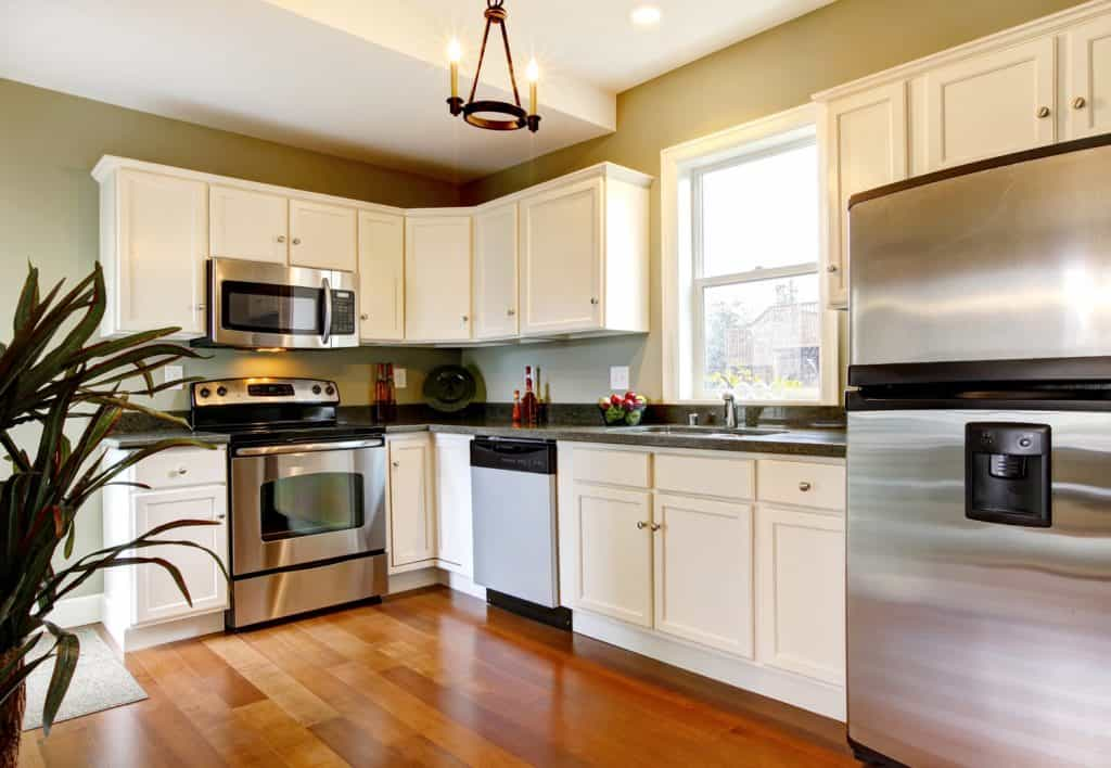Classic white and green new kitchen with cherry floor
