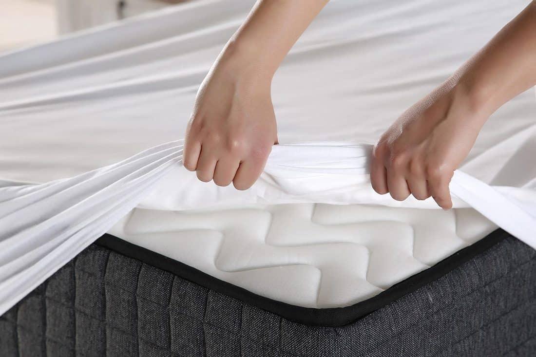 Female hand pulling white sheets