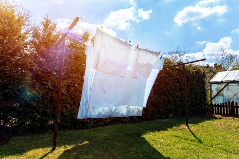 Hanging white bed sheets outside to dry in the sun, How To Dry Bed Sheets Fast Without A Dryer—4 Alternative Tried And True Methods