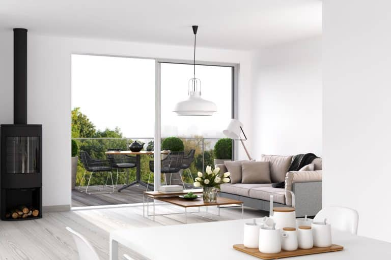 Interior of a modern white painted living room with a huge sliding door leading to a balcony, Which Way Should A Sliding Door Open?