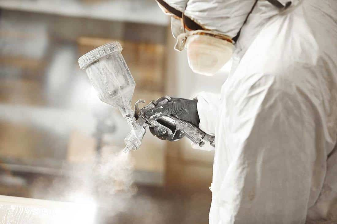 Man working with paint spray gun