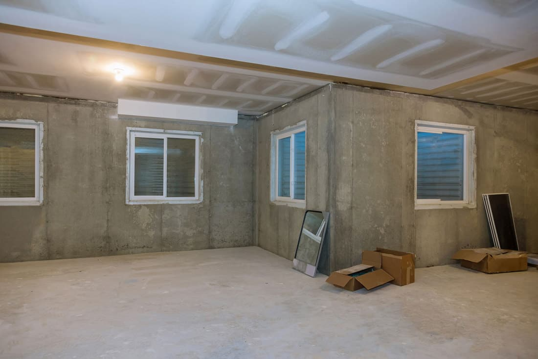 Unfinished view on concrete floor construction of basement empty under construction of residential home